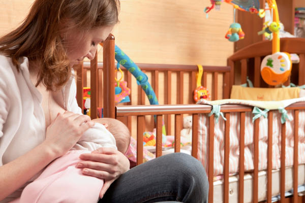 mother breastfeeding baby in nursery