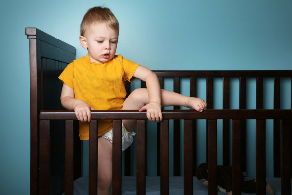 Child climbing out of cot