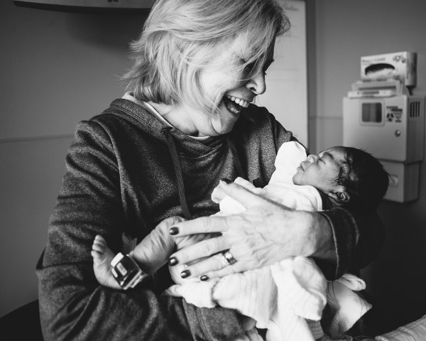 older woman holding newborn baby Blended project Kate T Parker