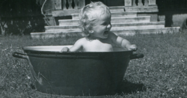 black and white photo of baby in an old bathtub outside