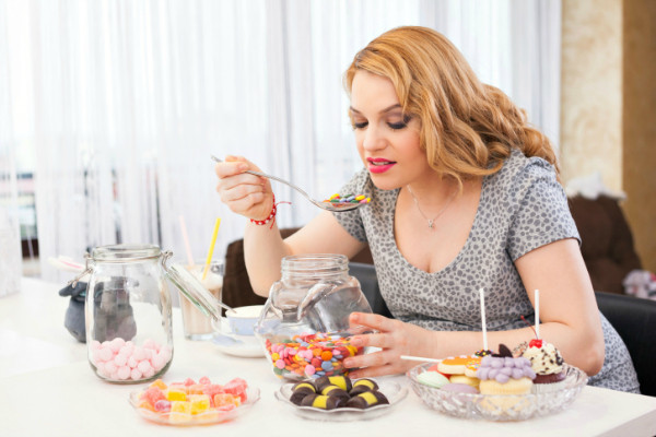 woman sitting at a kitchen bench eating sweets and desserts