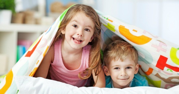 girl and boy siblings playing under quilt