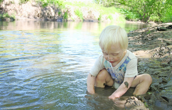 little boy playing in mud at river