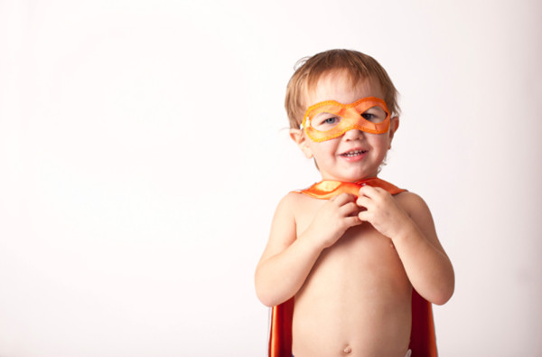 young boy dressed in superhero cape and mask