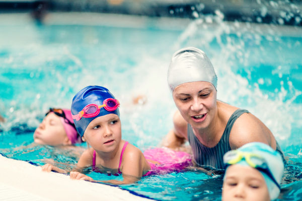 Instructor with children on swimming class