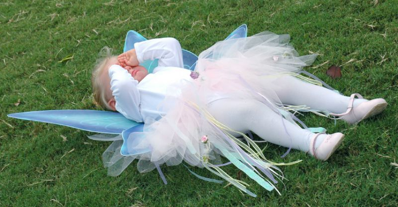 little girl in fairy dress lying on ground crying