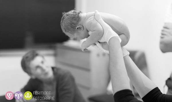 midwife holding newborn baby in her hands