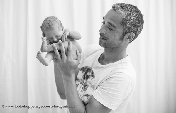 father holding newborn baby curled up in his hands