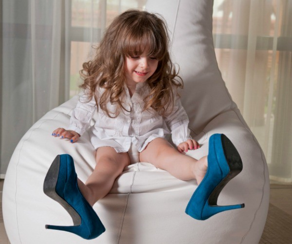 little girl trying on mum's blue high heeled shoes
