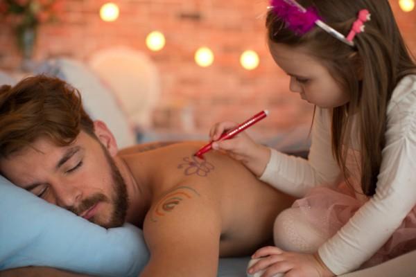 girl drawing on sleeping dad sl