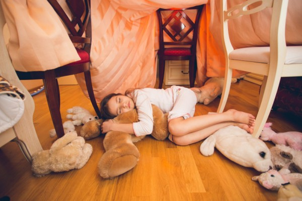 Beautiful cute girl sleeping on floor with toys at bedroom