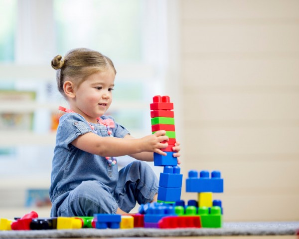 A little girl is sitting on the floor at preschool and is happily playing with colorful lego blocks .