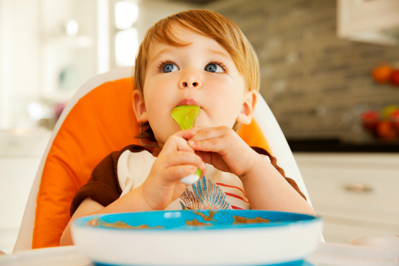 toddler boy eating meal in high chair