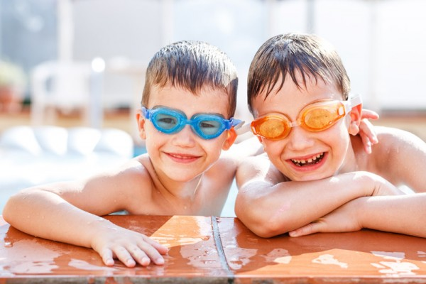 Boys laughing in pool with wet hair