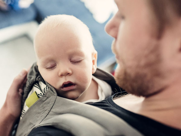 Father holding baby in carrier