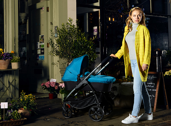 Woman standing next to pram with carrycot