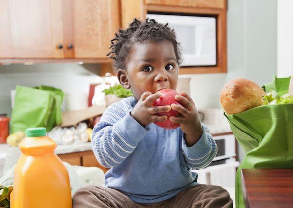 little boy eating apple in kitchen