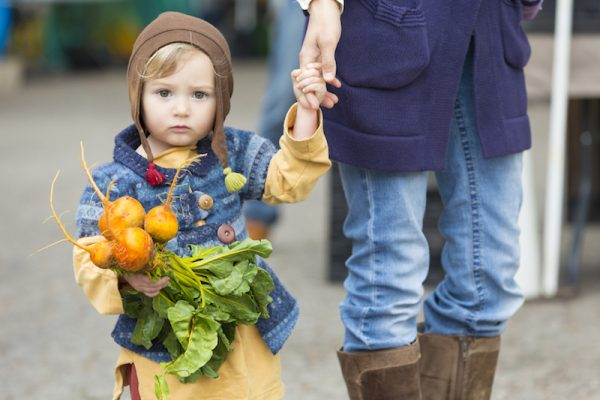 Adorable hipster child with beets at outdoor farmers market