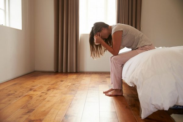 Woman with depression sits on edge of bed