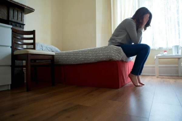 woman sad on edge of bed