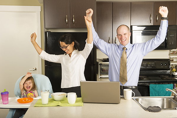 working parents cheering in kitchen with daughter