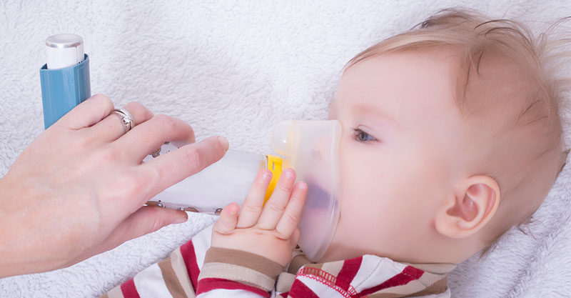 baby with asthma inhaler and spacer