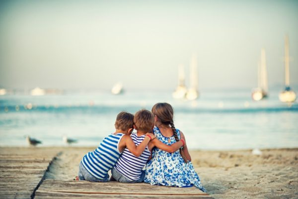 Children sitting on the beach, facing away from the camera