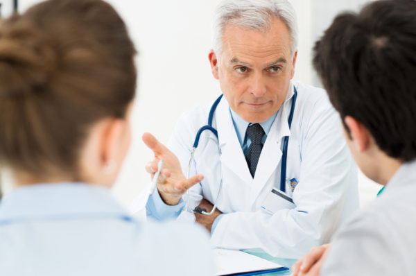 Mature Doctor Involved In Serious Discussion With His Patients