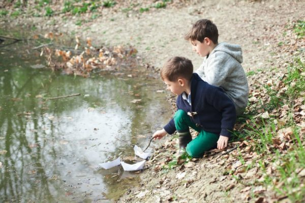 Boys playing with paper boats