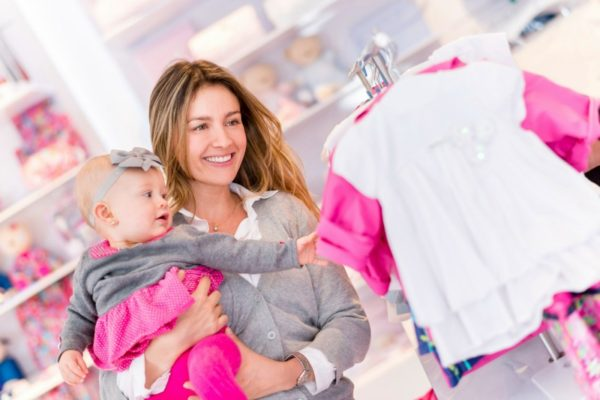 Woman shopping with a baby at a clothing shop