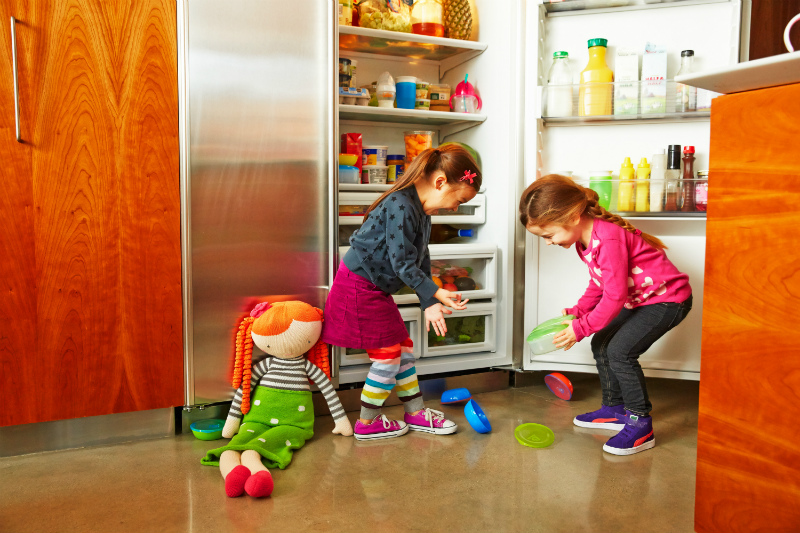 two young girls standing in front of open refrigerator