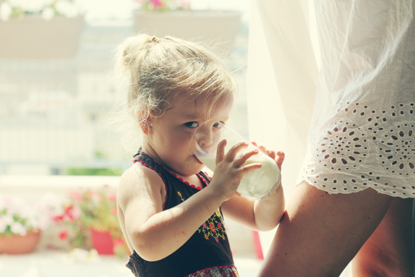 little girl drinking milk from glass