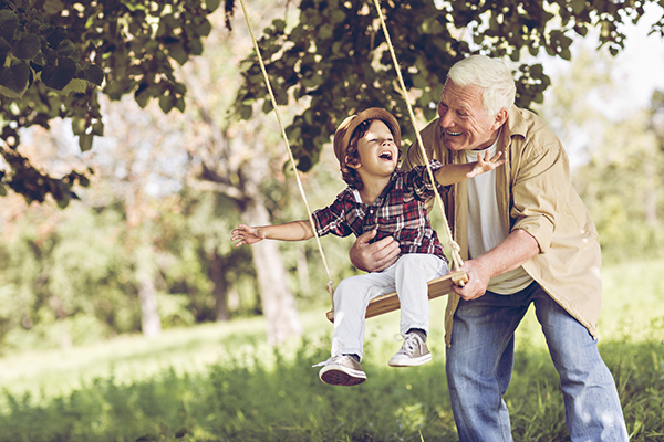 grandpa and boy playing on swing