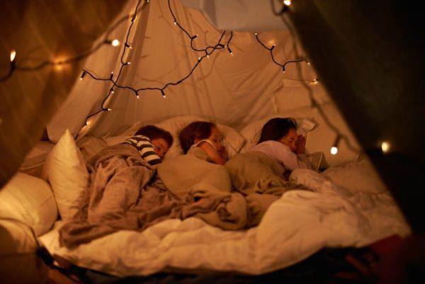 Shot of three young children sleeping in blanket tent