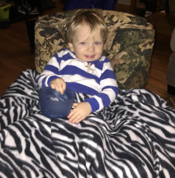 Hunter sitting under blanket at home