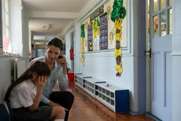 Mother comforts sad daughter at school