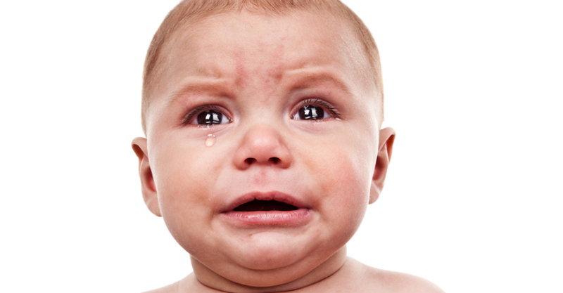 An 8 month old baby boy crying really big tears.