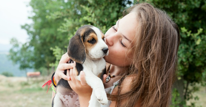 young girl kissing her puppy