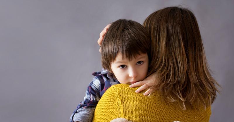 mother hugging a sad little boy