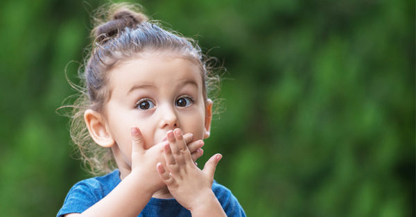 Little girl looking surprised with hands over mouth