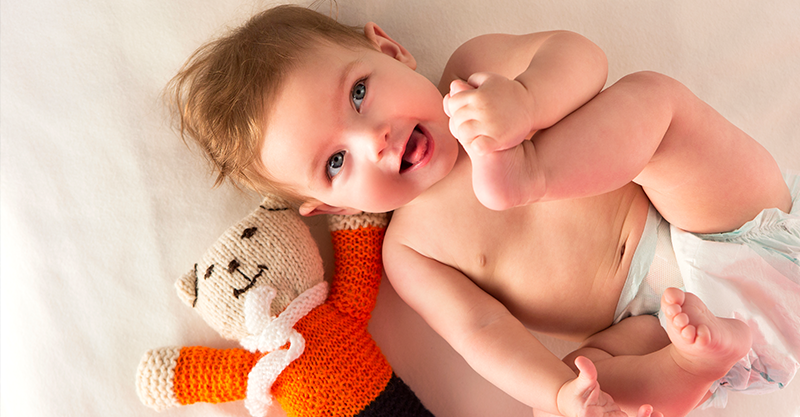 Smiling baby with knitted bear toy