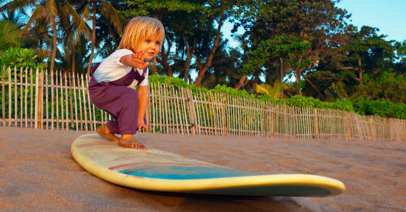 Boy standing on a surfboard