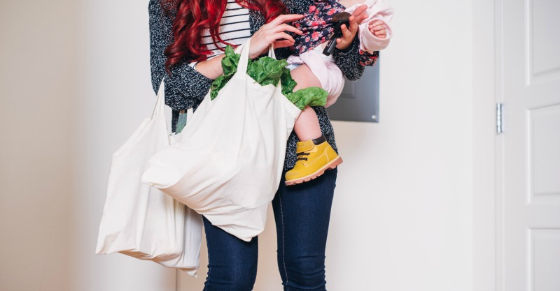mum carrying groceries and baby