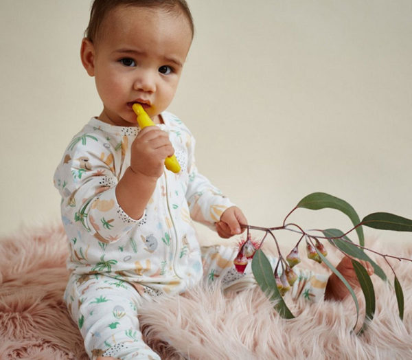 baby wearing Australiana romper suit with gum leaves