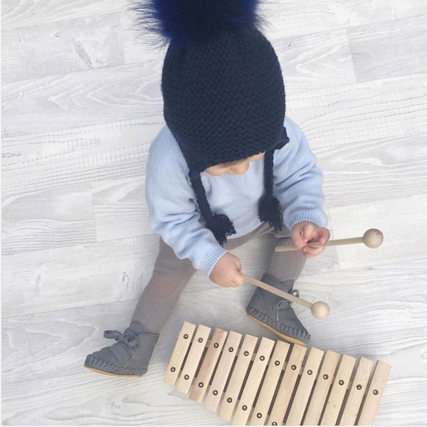 toddler wearing knitted beanie with pom pom
