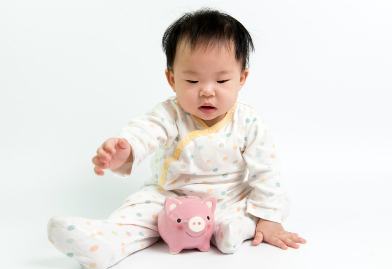Asian baby with pink piggy bank