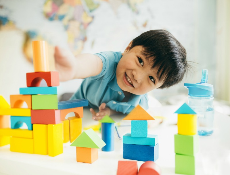 young boy playing with wooden blocks