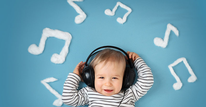 Toddler boy listening to music with headphones