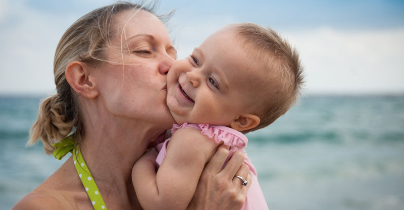 Mother kissing baby girl at the beach