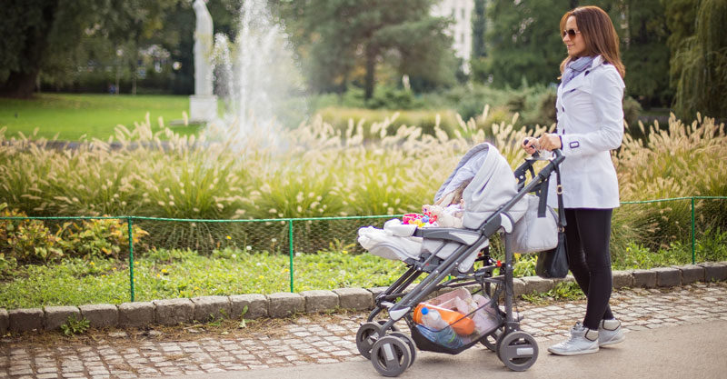 Mother with pram in front of fountain
